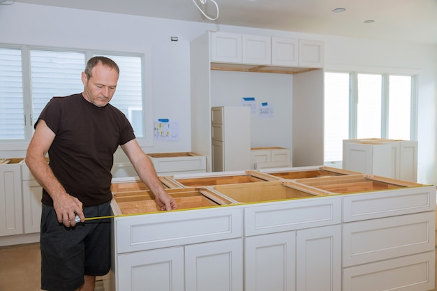 Mann, der maßband für das messen der größe in der modernen küche für heimwerker verwendet.