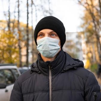 Mann, der medizinische maske in der stadt trägt