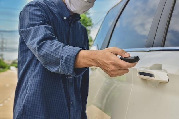 Mann, der medizinische maske trägt, öffnet autotür