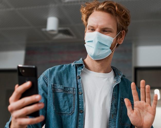 Mann, der medizinische maske trägt und das telefon betrachtet