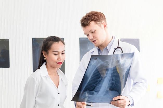 Mann der medizinischen fachleute, der röntgenstrahl und gespräch mit asiatischem patienten der jungen frau hält.