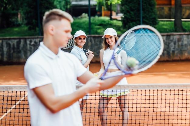 Mann, der mit beiden händen einen tennisschläger schwingt, um einen starken schlag zu machen. üben sie nachts vor einem spiel.