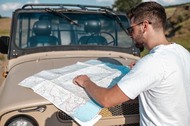 Mann, der mit dem auto reist und karte überprüft