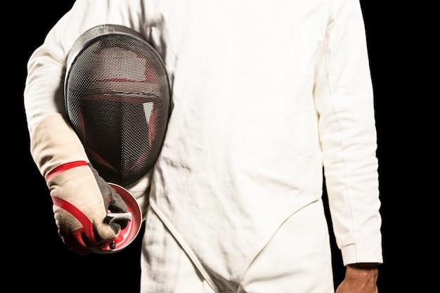 Mann, der mit dem fechten der maske steht