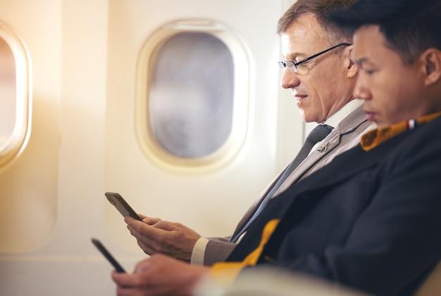Mann, der mit dem flugzeug und unter verwendung des mobiltelefons, konzeptinternet in der luftstratosphäre reist