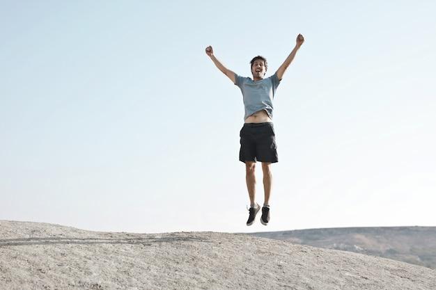 Mann, der mit den armen nach oben springt und freiheit oder erfolg darstellt