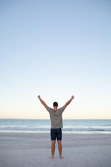 Mann, der mit den armen oben auf dem strand steht