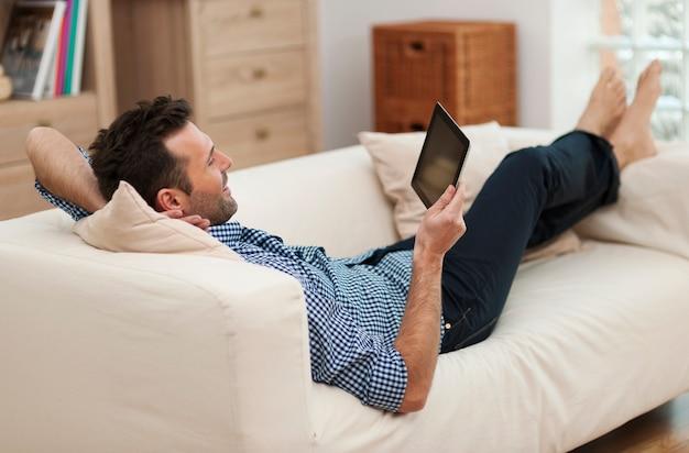 Mann, der mit digitalem tablett zu hause entspannt