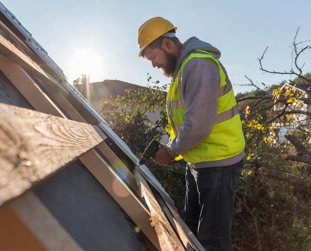 Mann, der mit einem bohrer auf dach arbeitet