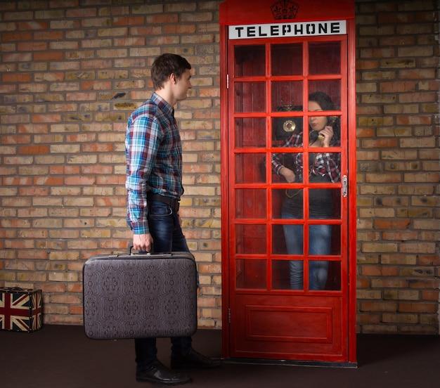Mann, der mit einem koffer wartet, während seine frau in einer roten britischen telefonzelle ein telefon anruft
