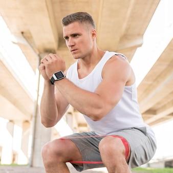 Mann, der mit einem stretchingband arbeitet
