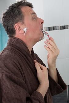 Mann, der mit einer rasierklinge und rasierschaum im badezimmer rasiert