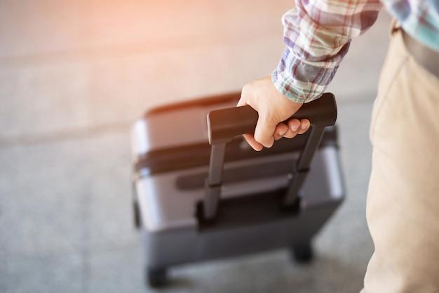 Mann, der mit gepäck geht. reisender, der koffer zieht, nahaufnahme