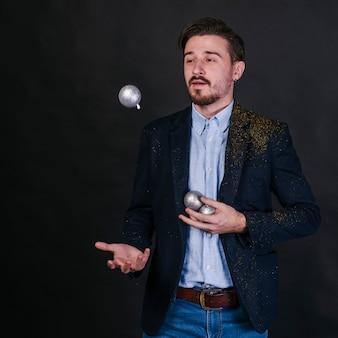 Mann, der mit glänzenden kugeln jongliert