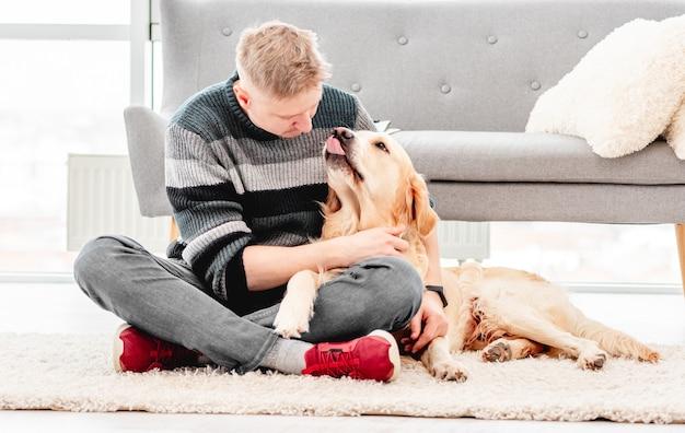 Mann, der mit goldenem retrieverhund sitzt und ihn auf dem boden umarmt. doggy küsste besitzer