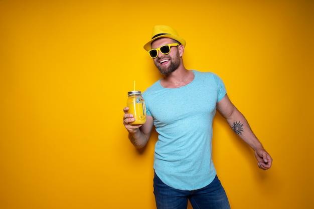 Mann, der mit hellem orangensaftgetränk aufwirft