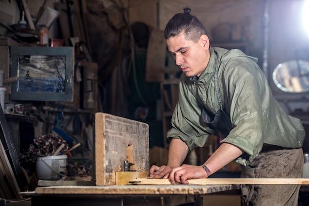 Mann, der mit holzprodukt auf der maschine arbeitet