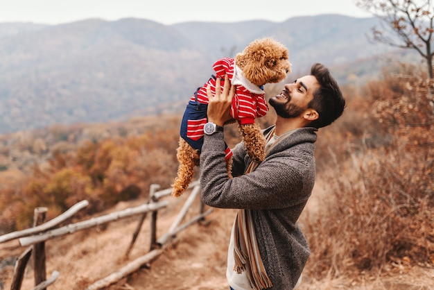 Mann, der mit hund in der natur spielt. im hintergrund wald und berge. herbstzeit.