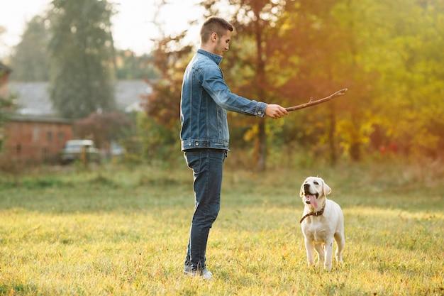 Mann, der mit hund labrador im park bei sonnenuntergang spielt