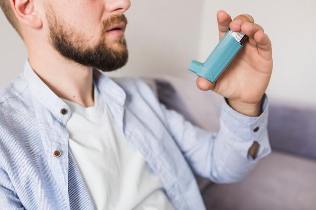 Mann, der mit inhalator sitzt