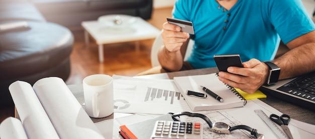 Mann, der mit kreditkarte am intelligenten telefon zahlt