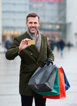 Mann, der mit kreditkarte für wintereinkauf zahlt