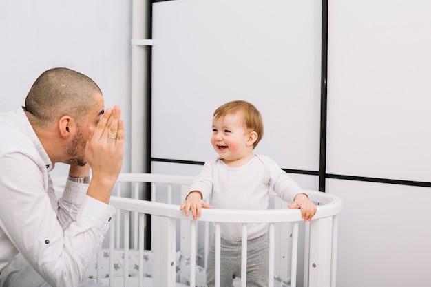 Mann, der mit lächelndem kleinem baby in der krippe spielt