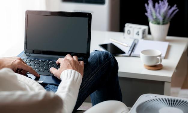 Mann, der mit laptop arbeitet, während er im wohnzimmer zu hause sitzt und von zu hause aus arbeitet.