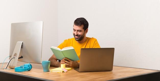 Mann, der mit laptot in einem büro ein buch lesend arbeitet