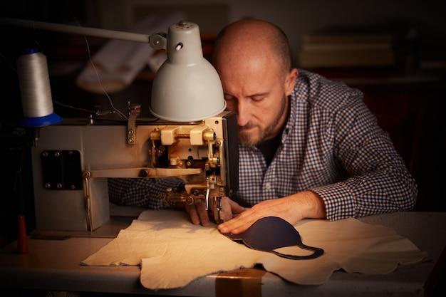 Mann, der mit nähmaschine arbeitet, die hausgemachte gesichtsmaske tut, um die ausbreitung des koronavirus zu verhindern und zu stoppen