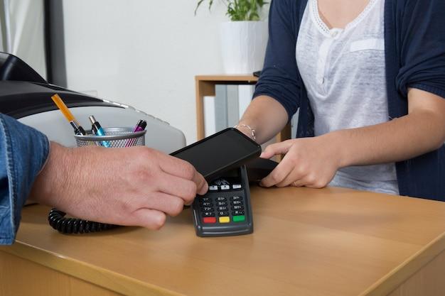 Mann, der mit nfc-technologie auf kreditkarte mit telefon, im restaurant, im geschäft bezahlt,