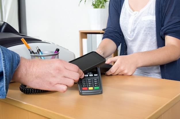 Mann, der mit nfc-technologie auf kreditkarte mit telefon, im restaurant, im geschäft zahlt