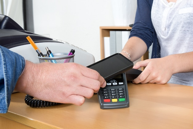 Mann, der mit nfc-technologie auf kreditkarte mit telefon, im restaurant, speicher zahlt,