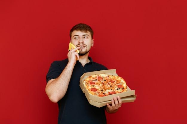 Mann, der mit pizzaschachtel in der hand steht und foto macht