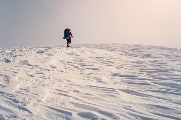Mann, der mit rucksack und schneeschuhen im winterberg wandert