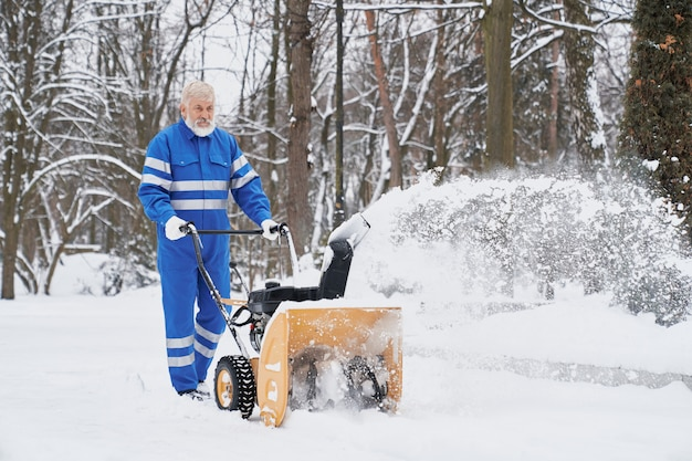 Mann, der mit schneefräse arbeitet und schnee vom fußweg entfernt