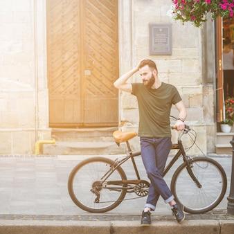 Mann, der mit seinem Fahrrad auf Bürgersteig steht