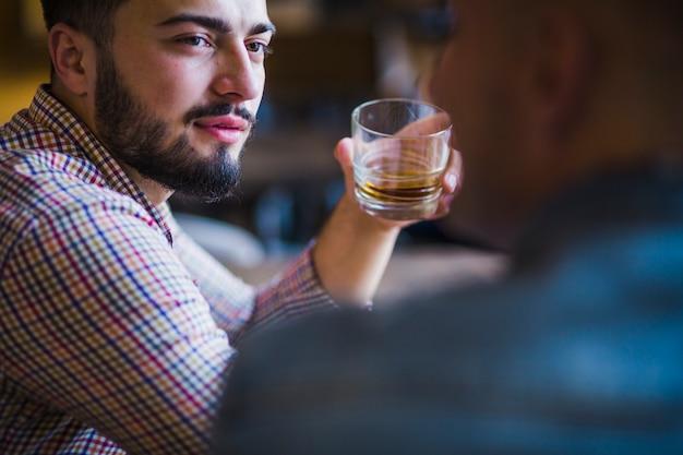 Mann, der mit seinem freund hält glas whisky sitzt
