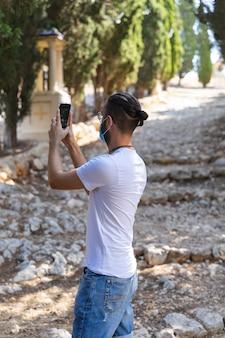 Mann, der mit seinem handy ein foto mit maske und weißem t-shirt macht