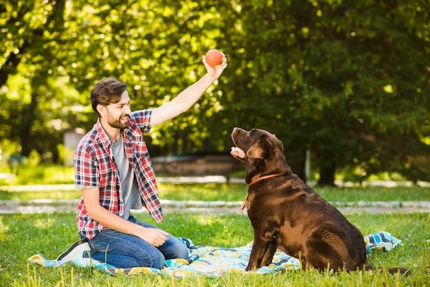 Mann, der mit seinem hund im garten spielt