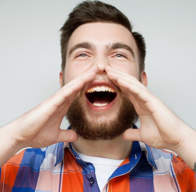 Mann, der mit seinen händen um seinen mund schreit