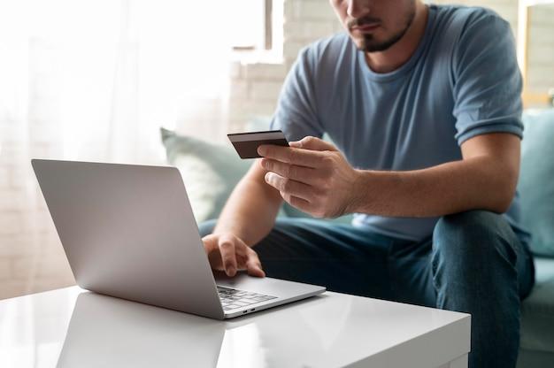 Mann, der mit seiner kreditkarte online um eine bestellung spielt