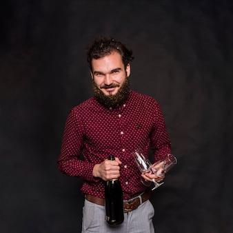Mann, der mit sektflasche und -gläsern steht