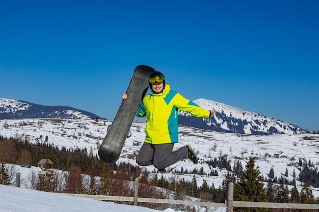 Mann, der mit snowboard in den händenbergen im hintergrund springt. sonniger tag. spaß haben