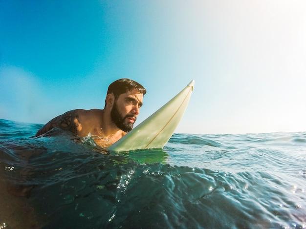 Mann, der mit surfbrett im blauen wasser steht