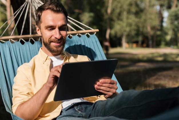 Mann, der mit tablette in der hängematte während des campings entspannt