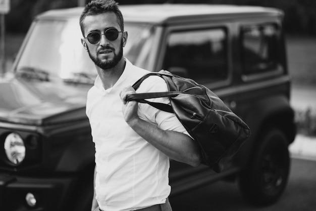 Mann, der mit tasche reist und durch das auto steht