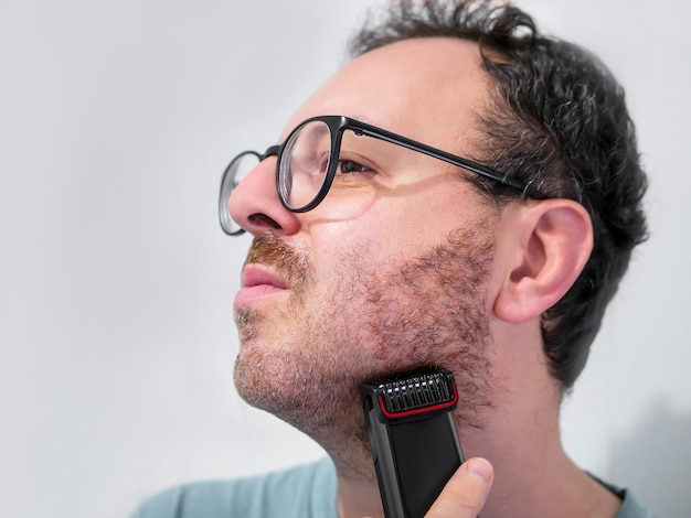 Mann, der mit trimmer, elektrorasierer sich rasiert