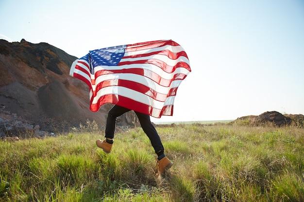 Mann, der mit usa-fahne in der natur läuft