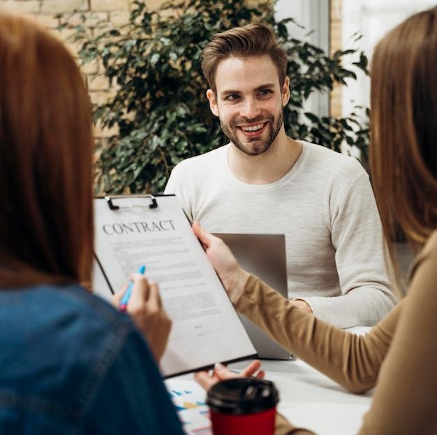 Mann, der mitarbeiter in einer besprechung anlächelt